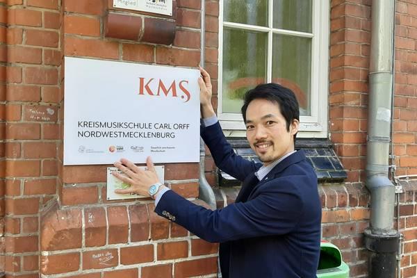 KMS-Direktor Hidehisa Edane zeigt, wo das neue Logo an der Kreismusikschule in Wismar hängen wird.