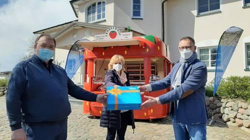 WEMACOM Geschäftsführer Volker Buck (rechts) übergibt im Beisein von Landrätin Kerstin Weiss symbolisch den Router an Betriebsleiter Jan van Leeuwen auf dem Erdbeerhof Glantz.