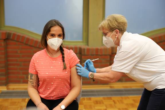Kathy Wienecke, Leiterin der Kindertagesstätte Am Tannenberg erhält ihre Impfung von Schwester Susanne Kugel.