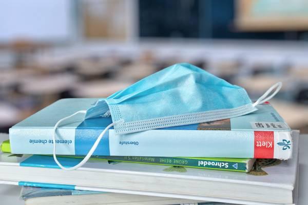 Ein medizinischer Mundschutz liegt auf Büchern